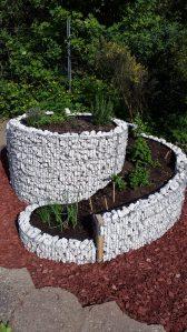 Bepflanze Kräuterspirale mit Kräutern